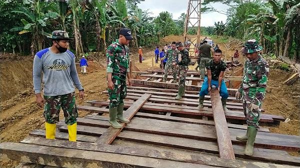 Sertu Edi Hermawan Personil Satgas TMMD Memberikan Intruksi Untuk Pengaturan Pemasangan Papan Lantai Jembatan
