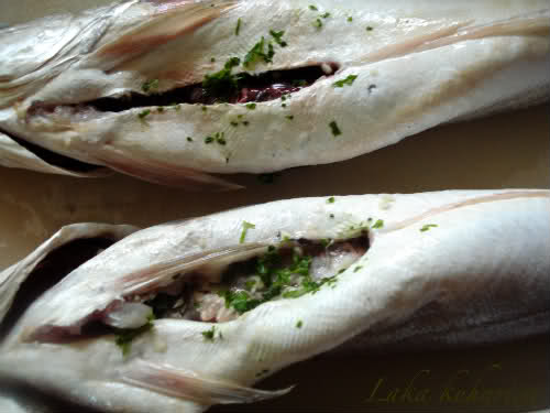 Oven-baked hake with vegetables and lovage by Laka kuharica: Fill the fish cavity with parsley, lovage and garlic