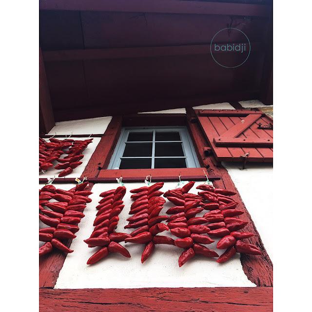 Piments d'Espelette suspendus à la fenêtre d'une maison basque rouge