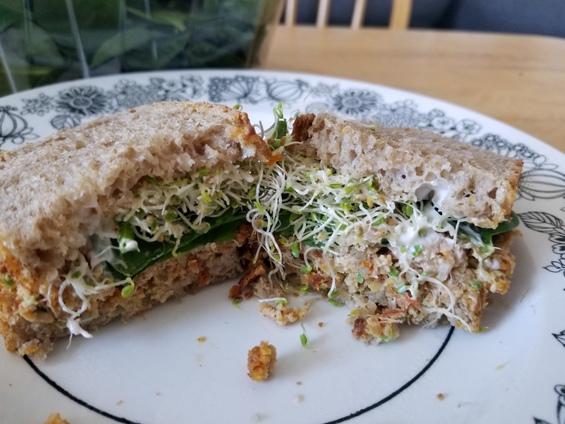 En sandwich avec pain maison, luzerne, verdure, mayo et moutarde