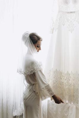 Novia con velo y una bata admirando un vestido