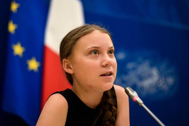 A imagem mostra a ativista sueca Greta Thunberg na Assembléia da ONU. Ela é caucasiana, tem olhos verdes, usa uma blusa preta, está com uma trança de lado e fala em frente a um microfone na ONU.