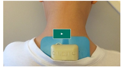 Screen capture from a video, showing the back of a person's neck  with a small buzzing device attached with a gel pack