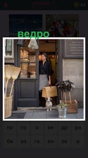 в дверях стоит женщина с собакой и рядом поставлено обычное ведро