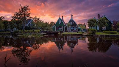 Precioso lago con casas de fondo y atardecer con arboles