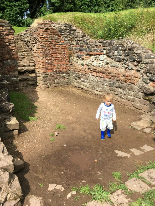 Caerleon-the-roman-fortress-of-isca-a-toddler-with-ruins-behind-and-puddle-in-front