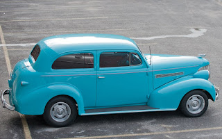 A vintage 2 door sedan in bright turquoise.