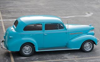 A vintage 2 door sedan in bright turquoise.