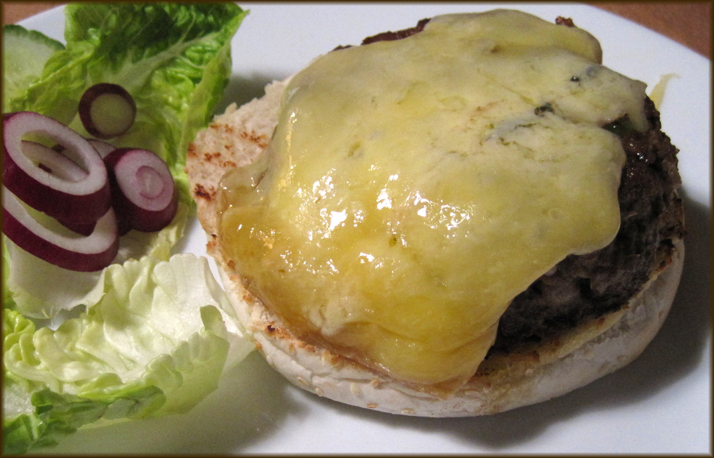 Melting cheese on top of burger with side salad