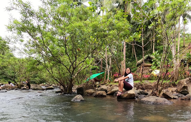 girl sitting beside a clear river with nipa hut at the back