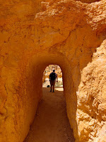 Long empty tunnel through golden rock with back of man at the far end