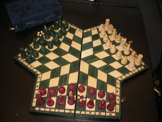 A wooden board that looks vaguely like a trefoil with squared-off leaves. Each player's section is four rows, warped into a pentagonal shape with the central columns stretching in length to reach the centre of the board, where the three sections meet. The closest section is occupied by the normal chess pieces, in red, whilst the pieces on the far right section are white and the ones on the far left are green.