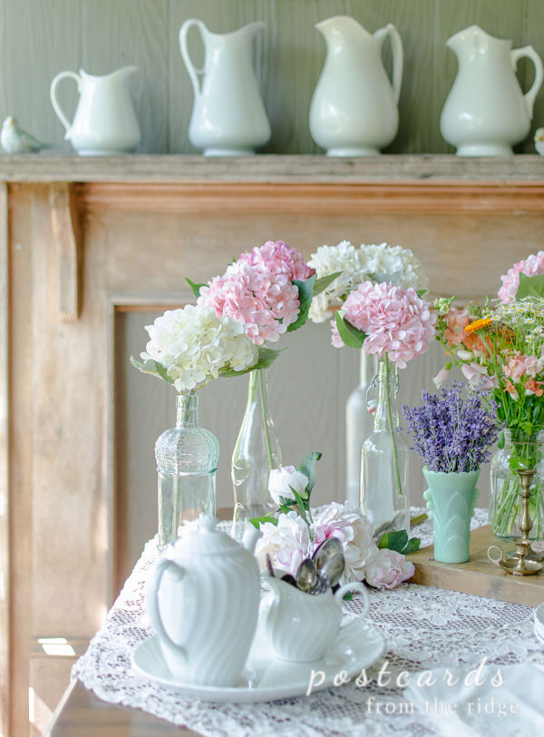 faux hydrangeas in glass bottles with vintage lace