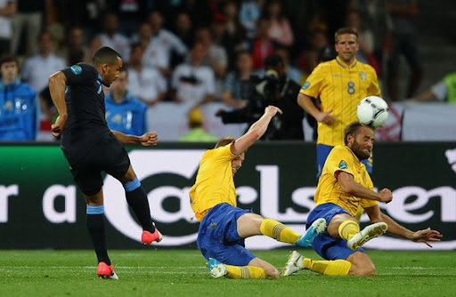 English player Theo Walcott kicks the ball to score a goal against Sweden
