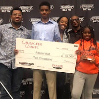 Adonis holding a big check for $10,000 from Parker and Sons Character Counts scholarship fund.  He's surrounded by his family.