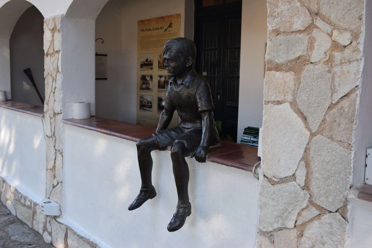 estatua de menino sentado na varanda