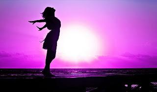 Silueta de mujer de perfil sobre paisaje de playa en tonos violeta con un gran sol recibe una bocanada de aire de pie con los brazos hacia atrás