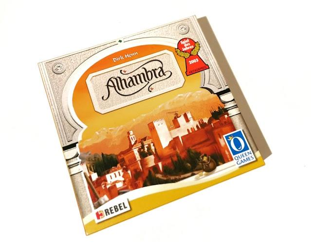 pudełko gry alhambra z rysunkiem miasta alhambra  kolorze pomarańczowym, wokół pudełka ramkę tworzą filary pałacu