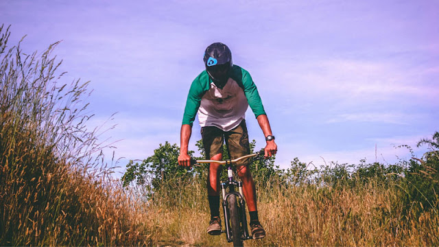 Man with helmet biking through tall grass
