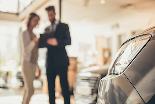 Car salesman showing paperwork to a customer.