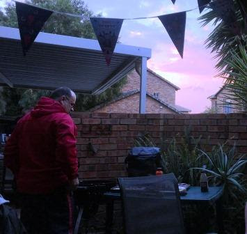 Man standing at barbecue with the sun setting, and Vampirina party flags