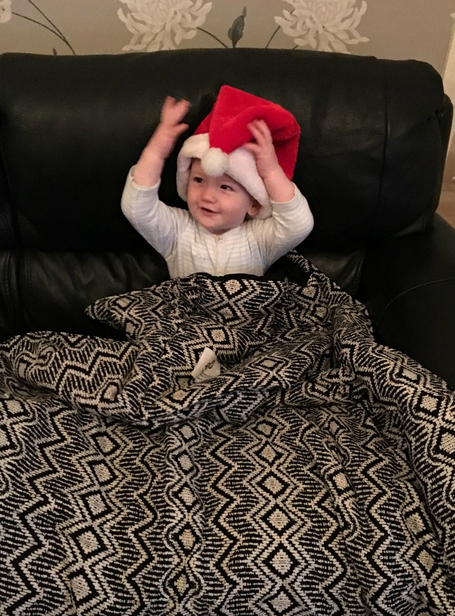 Christmas-gift-guide-2018-secret-projects-secret-piloow-in-black-and-white-on-sofa-opened-out-with-baby-wearing-santa-hat