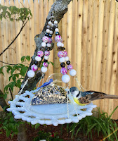 Vintage glass plate bird feeder with repurposed pink and silver jewelry accents, a colorful hanging decoration for your garden and yard!