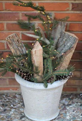 Vaso com ramos, luzes, lenha e pinhas