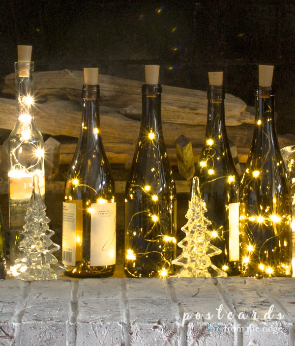 empty wine bottles with fairy lights on a painted brick hearth