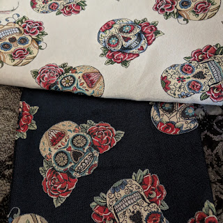 Two fabrics laid next to each other, of the same print but one with cream background, the other dark navy (looks black in the photo due to poor lighting). The print is of large decorative skulls with roses either side. There are details like flowers, gems and swirls on the skulls.