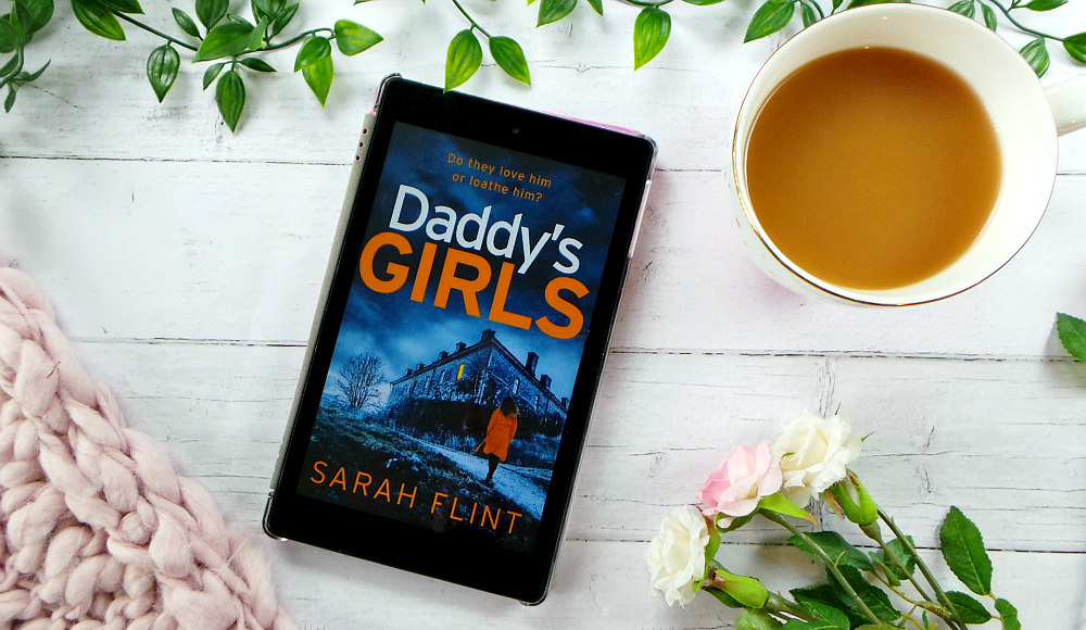 Kindle fire screen showing the cover for Daddys Girls. The cover has a women wearing an orange coat walking towards a building. The background of the image features some leaves, roses, cup of tea and a pink chunky knit blanket