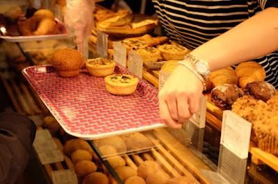 東京 パン、カフェ 365日 パンをトレイにとる店員さん