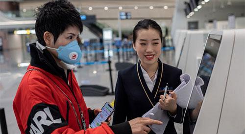 Seorang pelancong menerima bantuan check-in dari staf maskapai di Bandara Internasional Daxing. Foto Nicolas Asfouri / AFP / Getty Images