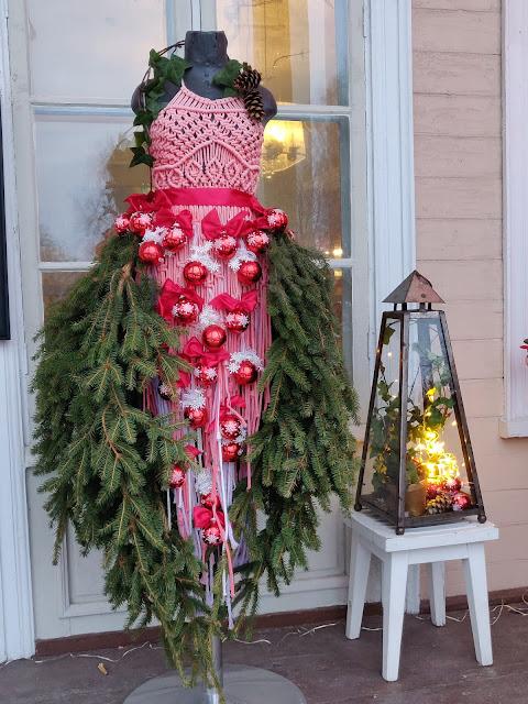 Kuvassa jouluisesti koristeltu mallinukke ja lyhty