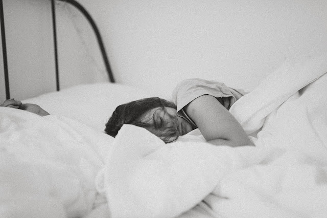 Sleeping woman in bed with white bedclothes