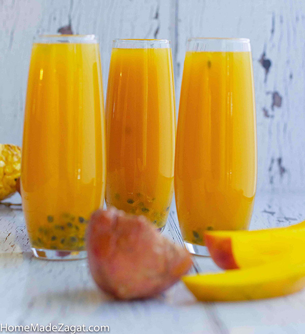 Passion fruit juice in glasses with passion fruit and mango slices in front