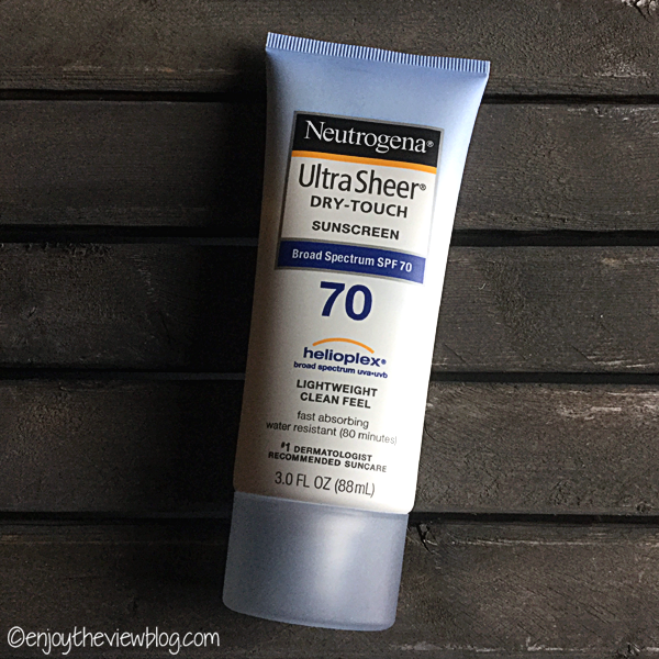 A tube of Neutrogena Ultra Sheer® Dry-Touch sunscreen lying on a wooden table