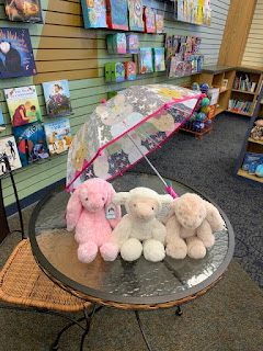 plush bunnies and a plush lamb sit under an clear umbrella with pink trim and pastel cartoon mice