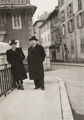 Richard and Alice Neumann in black coats and hats stand on a sidewalk by a wroght iron fence.