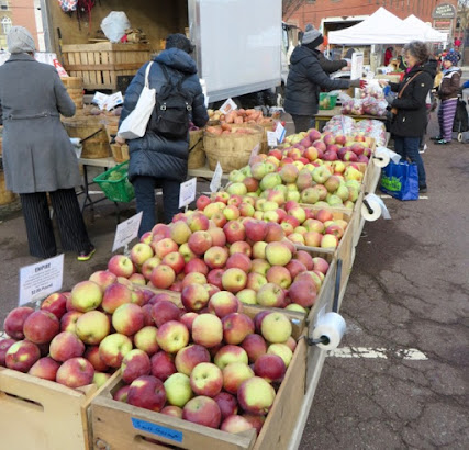 Different apples in different bins near a different truck, with some bundled-up shoppers.
