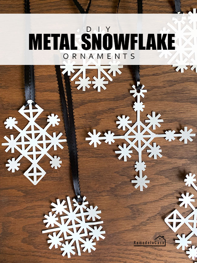 metal snowflakes with black ribbon on wooden surface