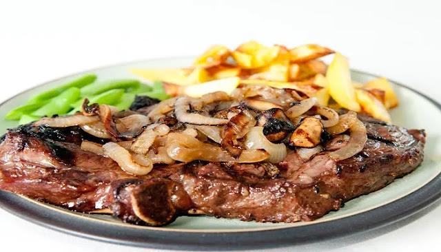 Carne asada a fuego lento, acompañada con papas y cebollas