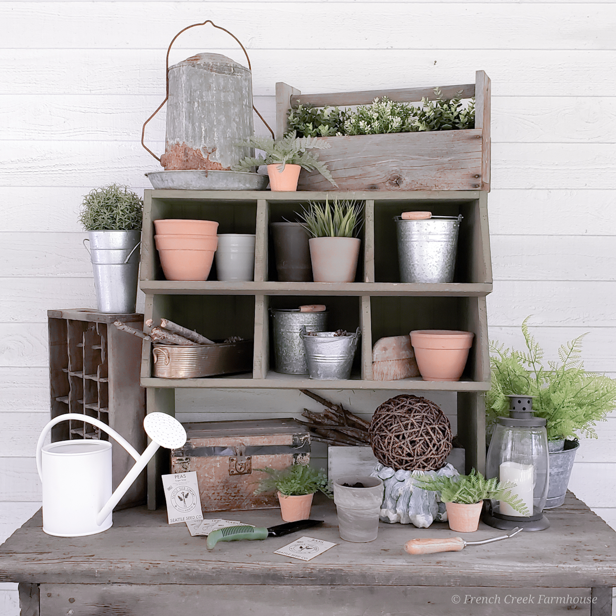 I combined a rustic wood table with a chicken nesting box to create our potting bench