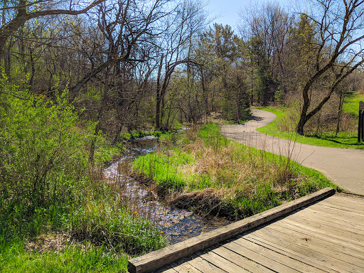 wood bridge over stream leading to paved trail