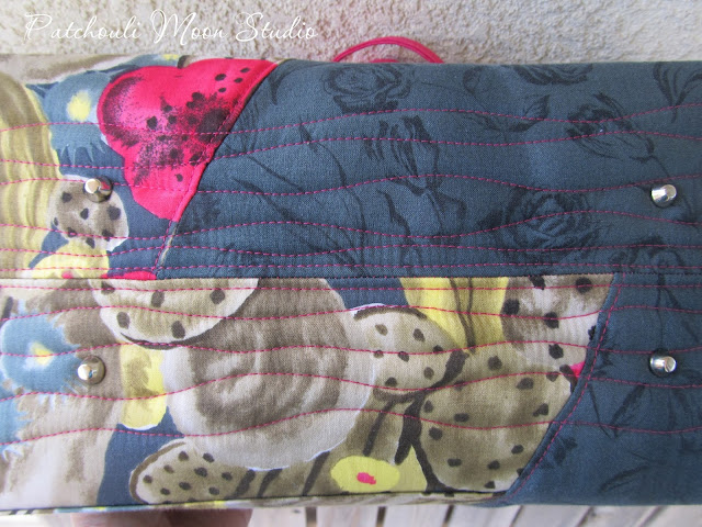 Bottom of tote bag is quilted with added purse feet