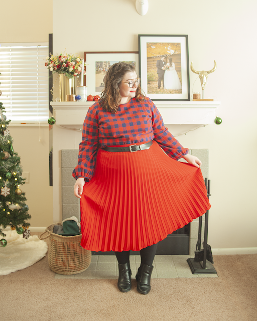 An outfit consisting of a red and navy blue buffalo plaid blouse tucked into red pleated tea length skirt.