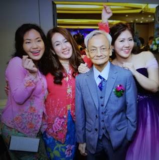 father and daughters wearing kebaya