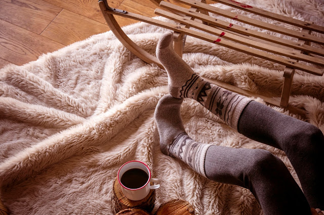 A cosy fleece with a lady lying on it, with just her feet in view, wearing thick socks with a cup of coffee beside her