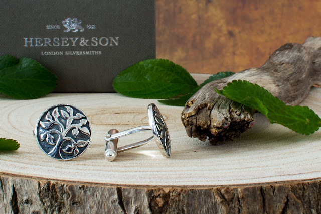 Close up of silver cufflink father's day gift idea with a tree etched on them from Hersey & Son on some wood with leaves