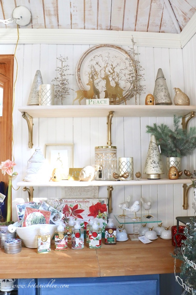 New open shelves with gold bracket supports filled with items for sale in the French Country Christmas Event